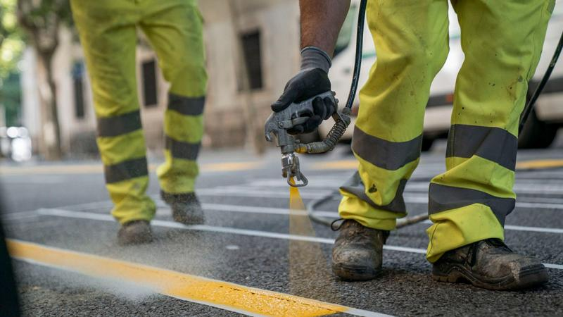 A worker specialising in road markings painting yellow lines on a road surface