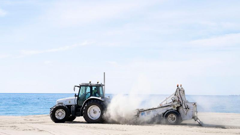 A municipal worker in a tractor preparing the sand at Bogatell beach