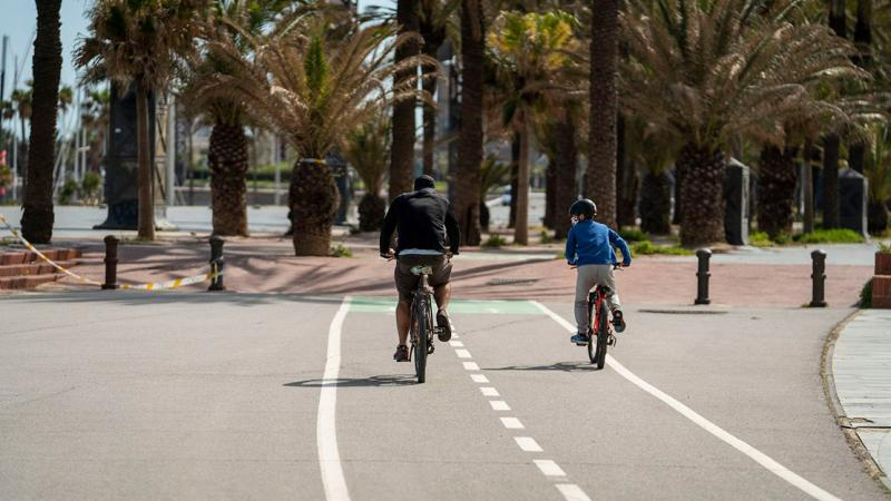 A family with the father and boy cycling along the bicycle lane