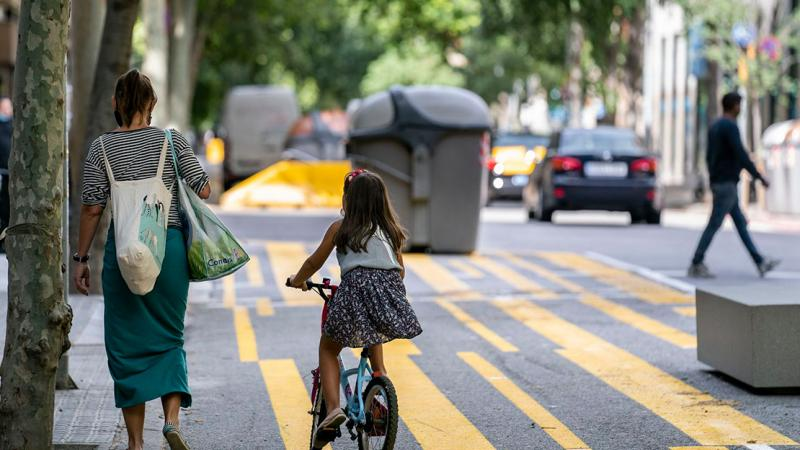 A family with the mother carrying bags and a girl on a bike using the extended pedestrian area on Carrer del Consell de Cent and passing by some new benches
