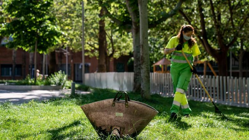 "A female ""Barcelona for the Environment"" worker raking a landscaped area"
