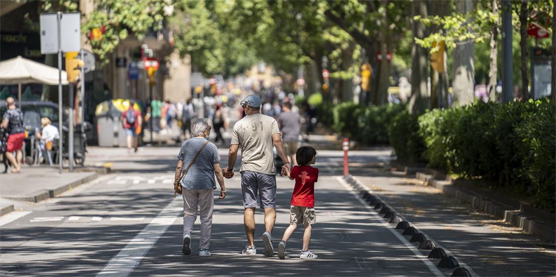 Una família amb l'àvia, un adult i un nen passegen pel mig del passeig de Sant Joan, que forma part de la xarxa d'itineraris segurs © Ajuntament de Barcelona / Goroka