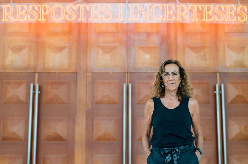 """Carme Portaceli davant unes portes amb un cartell que diu """"Respostes i incerteses"""". © Clara Soler Chopo"""