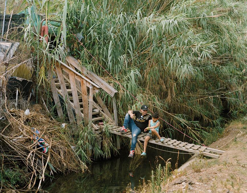 Un adult i un nen asseguts sobre un pont improvisat que travessa el Rec Comtal en passar per Vallbona, l'únic tram al descobert d'aquest rec i que encara proveeix d'aigua els horts urbans de la zona. © Myriam Meloni i Arnau Bach