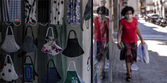 Una dona camina per un carrer al voltant de la plaça de la Vila de Gràcia i passa per davant de l'aparador d'una botiga on venen mascaretes d'ús no sanitari. © Laura Guerrero