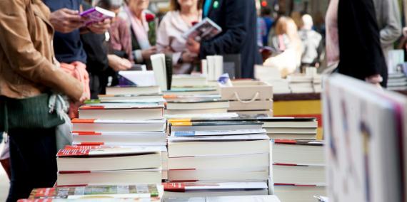 Personas alrededor de una parada de libros en la calle