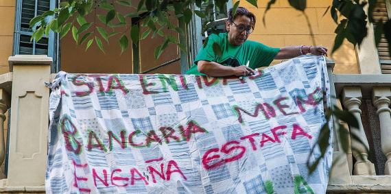 Una dona penja una pancarta al balcó de casa seva en la qual es llegeix: banca estafa engaña © Pere Virgili