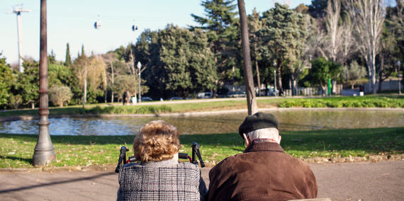 An elderly couple sitting on a bench looking at a pond