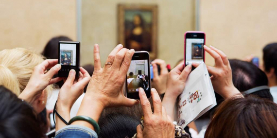 Hands of people taking pictures of La Gioconda with their cellphones.