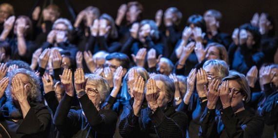 Older women singing while performing a choreography with their hands. © Laura Guerrero