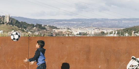 © Leo García. Barri de la Trinitat Nova: Un nen amb una pilota travessa el pont de la Meridiana i darrera es veu una dona amb un cotxet.