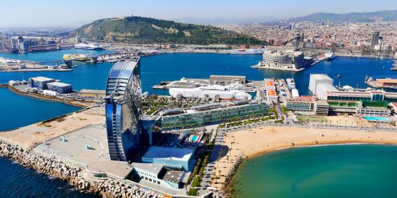 Vista des del mar de Barcelona amb la plaça de la Rosa dels Vents, l'Hotel W i una part de la platja de Sant Sebastià, en primer pla, i Montjuïc i el World Trade Center, al fons. © Hemav. Ajuntament de Barcelona.