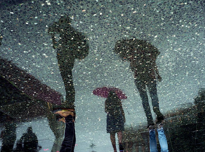 L'ombra de tres persones que duen paraigües reflectida sobre un terra de marbre. © Sergi Capellas