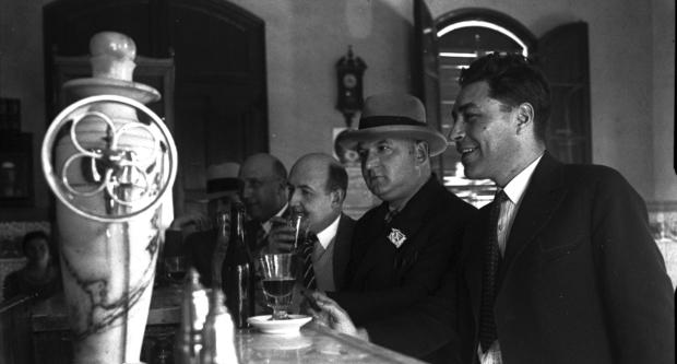 ANC / Gabriel Casas i Galobardes / D'esquerra a dreta, el periodista Josep Maria Planes, l'editor Antoni Lòpez i Llansàs i els escriptors Josep Maria de Sagarra, Francesc Pujols i Josep Pla, davant del mostrador d'un bar, a Martorell / 1930