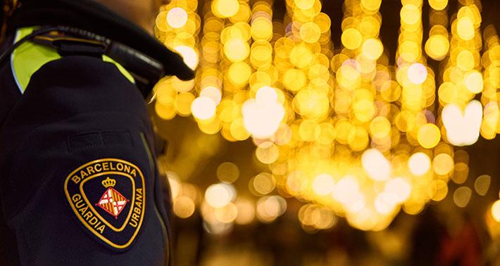 La Guàrdia Urbana patrullen per un carrer de Barcelona il·luminat amb motius nadalencs.