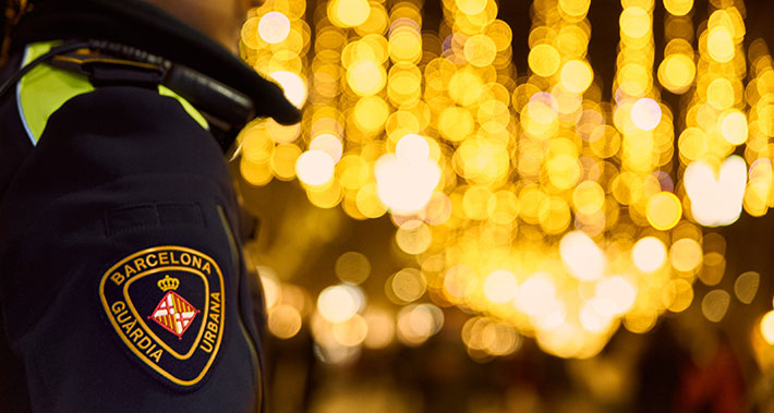 A Guàrdia Urbana police officer patrolling a street in Barcelona, which is decorated for Christmas.