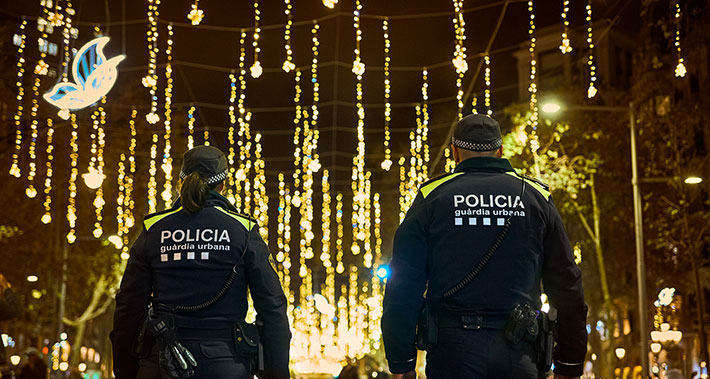 Two Guàrdia Urbana police officers patrolling a street in Barcelona, which is decorated for Christmas.