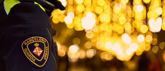A Guardia Urbana oficer patrols a street in Barcelona illuminated with Christmas motifs.