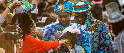 El rey Baltasar sostiene un bebé que una mujer le acerca antes de la cabalgata