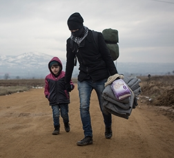 Father and child refugees walking along a sand path