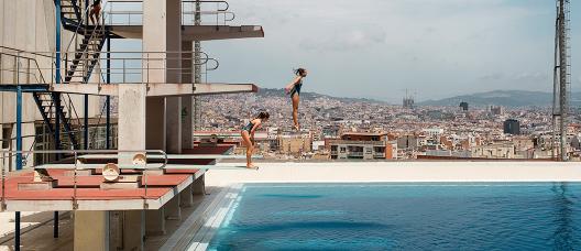 Dues noies salten d'un trampolí a les piscines Picornell