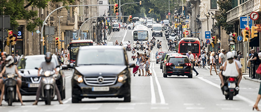 Vehículos circulan por una calle de Barcelona