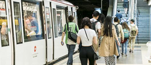Estació de metro amb el tren aturat i persones a l'andana