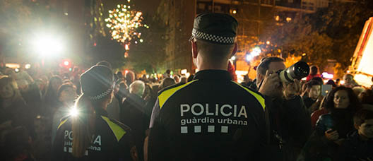 Two Guàrdia Urbana police officers in front of a crowd of people celebrating the Christmas festivities in the street.
