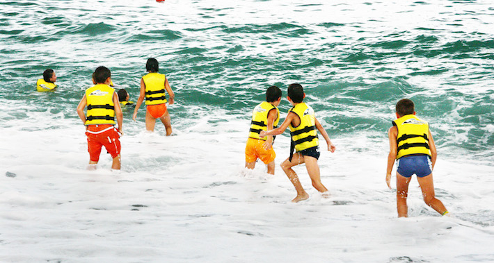 Group of youngsters swimming on the beach with life preservers