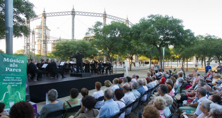 Public listening to an orchestra at a concert at a park
