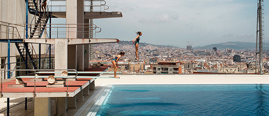 Two girls jumping off a trampoline in the Picornell swimming pools.