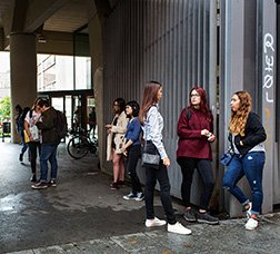 Groups of young people talking in the courtyard of a building.