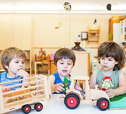 Tres infants juguen amb joguines de fusta en una escola bressol