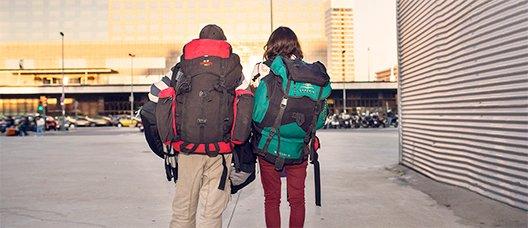Pareja con una mochila a punto de llegar a una estación de tren