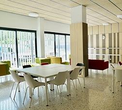 Comedor y espacio polivalente con mesas, sillas, sofás, butacas y un televisor