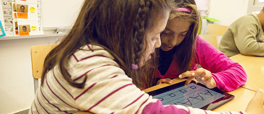Two girls in class, with a tablet, looking at vowels
