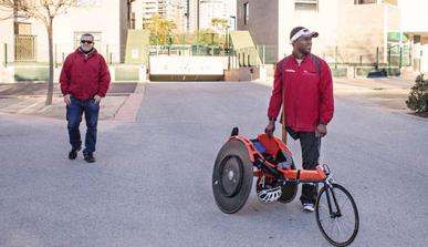 Joven sin pierna junto a su bicicleta adaptada