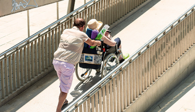 Man pushing a wheelchair along an access ramp to the beach