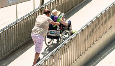 Un hombre empuja una silla de ruedas en una rampa de acceso a la playa