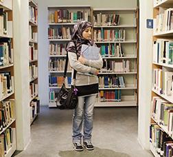 Chica árabe en una biblioteca mirando libros