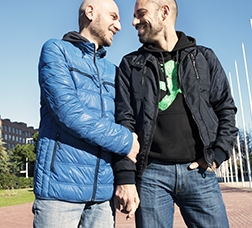 Homosexual couple holding hands and smiling at each other