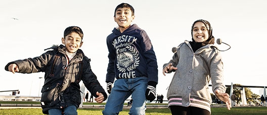 Kids of different nationalities jumping and laughing in a park