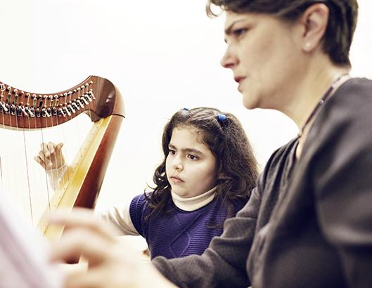 Niña en una clase aprendiendo a tocar el arpa