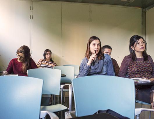 Grupo de personas adultas escuchando y tomando apuntes en una clase