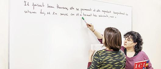 Profesora y alumna en la pizarra en una clase de francés