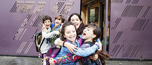 Grupo de niños y niñas a la salida de la escuela abrazándose y riendo
