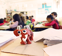 Clay elephant on a table and pupils in a class in the background