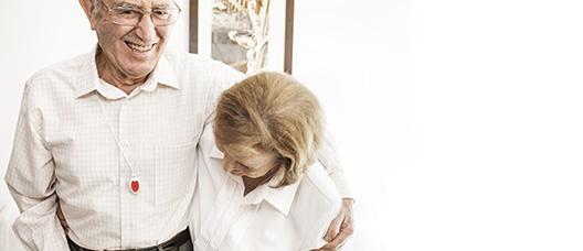 Matrimoni abraçat i rient amb el botó de la teleassistència penjat al coll