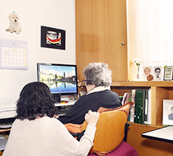 A woman sitting beside another aged over 65 looking at the computer