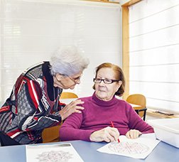 Two users in a day centre talking while they do a writing activity
